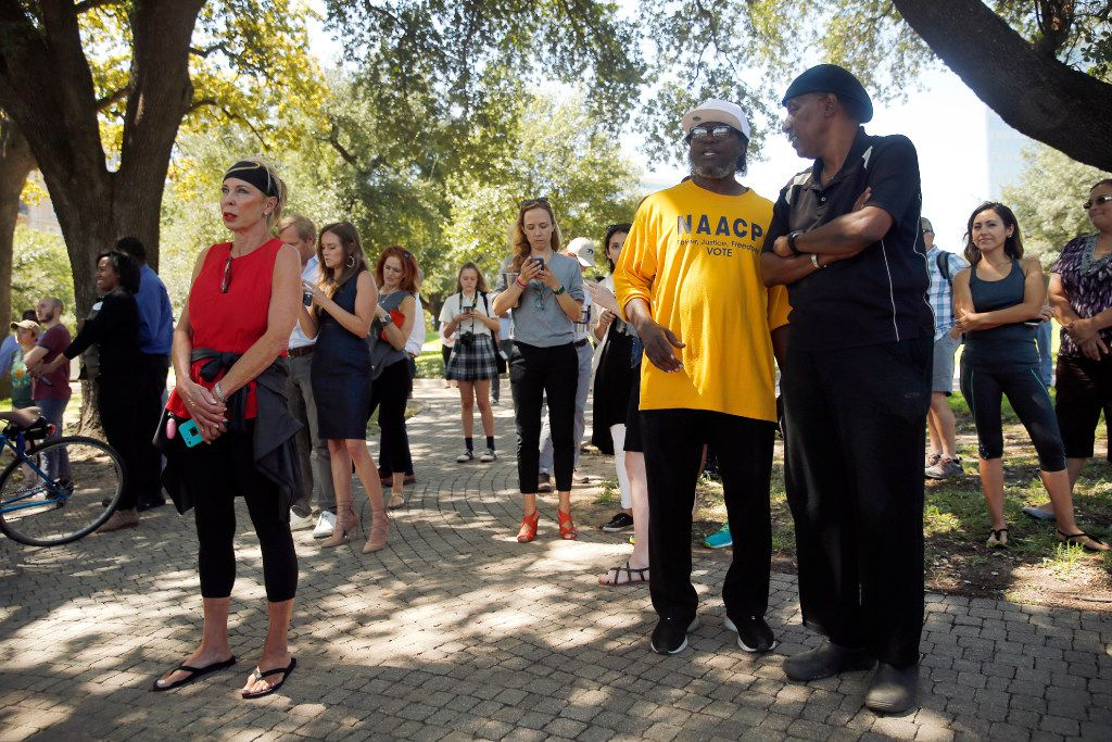 People gathered in the shade, including past local NAACP president Arthur Fleming (in yellow shirt) and pastor Clarence Glover Jr. of First African Freedom Church (right), to witness the removal of the Robert E. Lee statue from Robert E. Lee Park in Dallas, Wednesday, September 6, 2017. Earlier in the day the Dallas City Council voted 13-1 for immediate removal of the monument to the Confederate general with a soldier at his side. The removal was halted though by a temporary restraining order from U.S. District Judge Sidney A. Fitzwater. (Tom Fox/The Dallas Morning News)