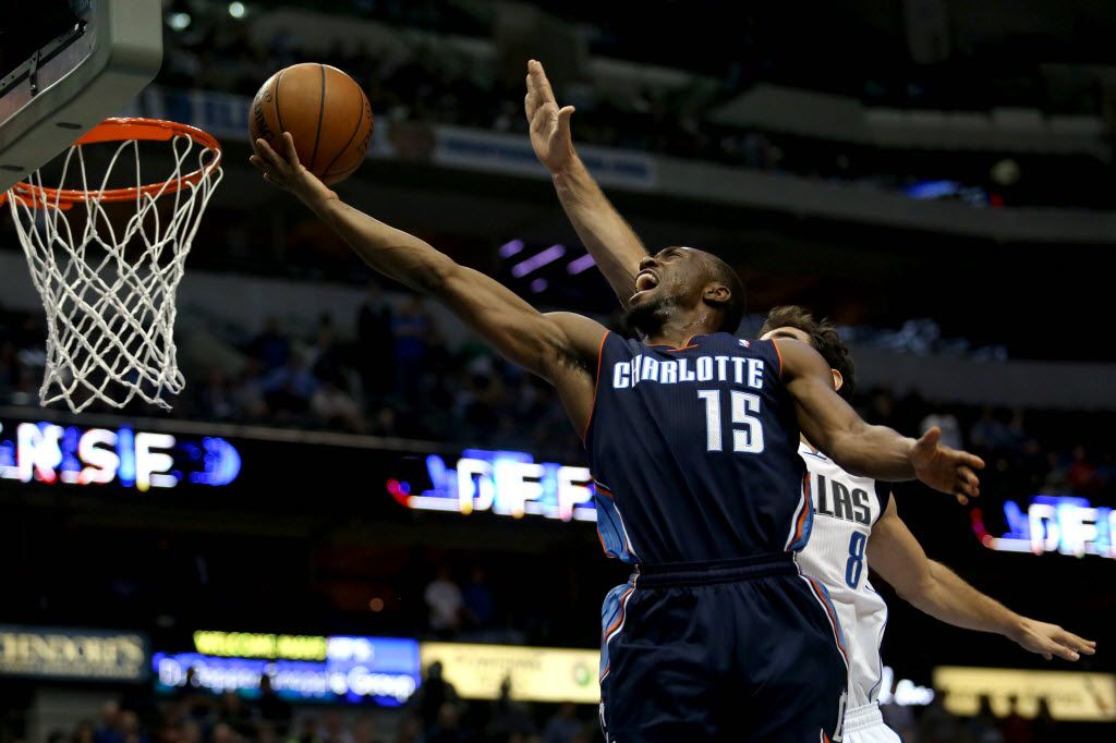 Charlotte Bobcats point guard Kemba Walker (15) goes up for a basket guarded by Dallas Mavericks point guard Jose Calderon (8) during the second half of NBA action on December 3, 2013 at American Airlines Center in Dallas. (Sarah Hoffman/The Dallas Morning News)