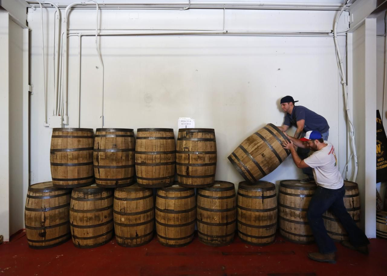 Tyler Doyle (top) and Chris Leurig  stack barrels of whiskey at the Witherspoon Distillery in Lewisville in 2013.