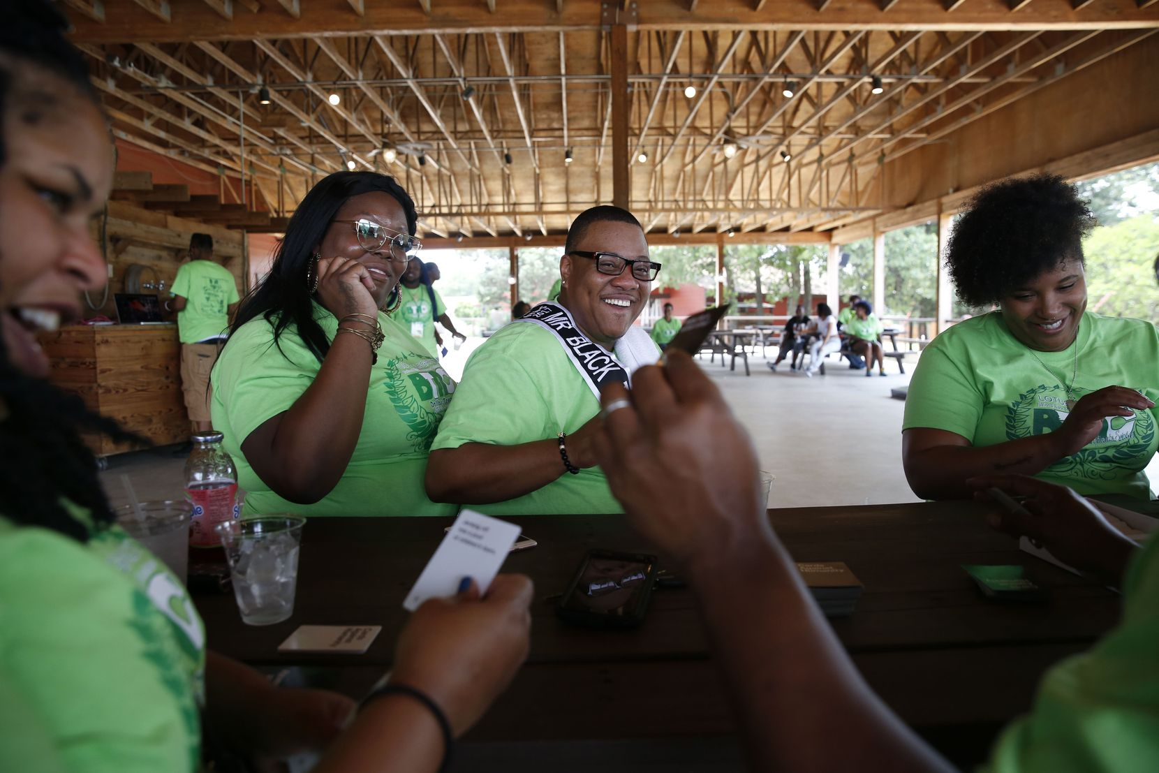 Trenton Johnson (center), a transgender man, sits with his fiancee Bridget Charleston (left) to play Cards Against Humanity with his friends during the Black Trans Advocacy Conference family day at Circle R Ranch in Flower Mound, Texas on Saturday, April 29, 2017.
