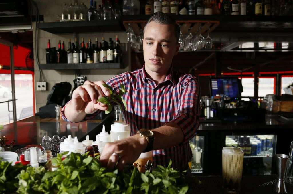 """Kyle Hilla, a bar manager at Bolsa restaurant in Dallas, picks a herb piece while he mixes a cocktail """"Mirage"""" on May 13, 2015."""