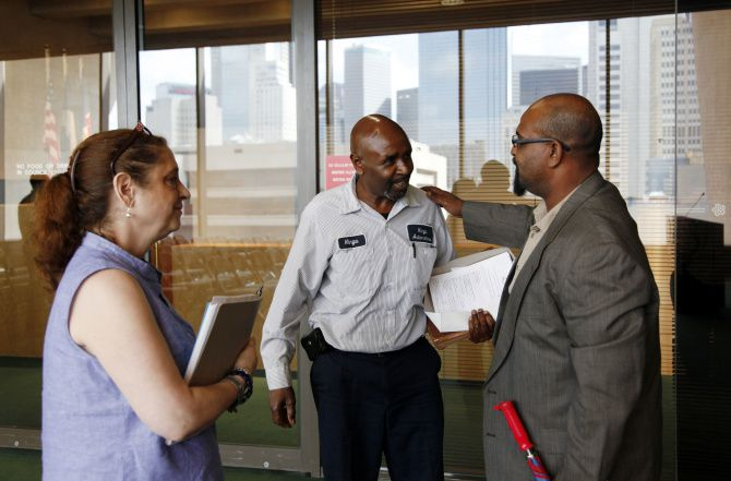 Auto repair shop owner Hinga Mbogo (center) was congratulated by supporters Gerald Davis and Angela Davis after successfully pleading his case before the Dallas Plan Commission.