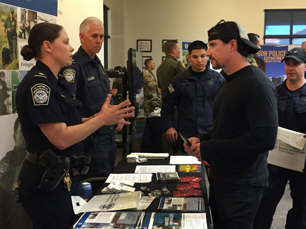 U.S. Customs and Border Protection recruiter Kelly Ursu talks with Michael Hamilton, a criminal justice graduate of Northern Arizona University, at a job fair in Tucson, Ariz. (2015 File Photo/The Associated Press)