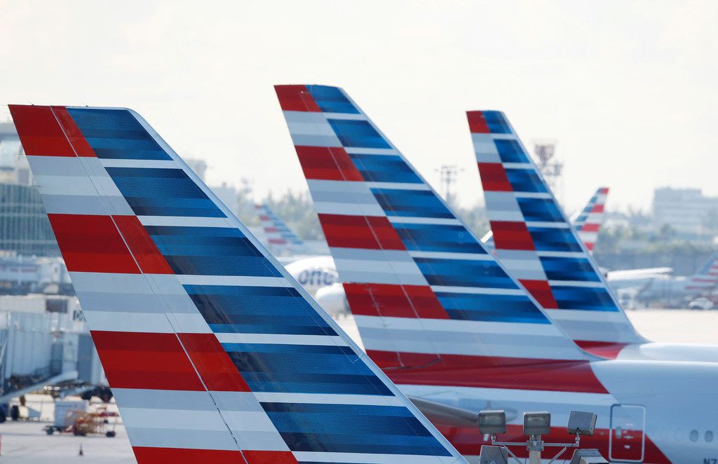 Painted vertical stabilizers are viewed as American Airlines jets are parked on the airport apron, Monday, Nov. 6, 2017, at Miami International Airport in Miami.  (AP Photo/Wilfredo Lee)