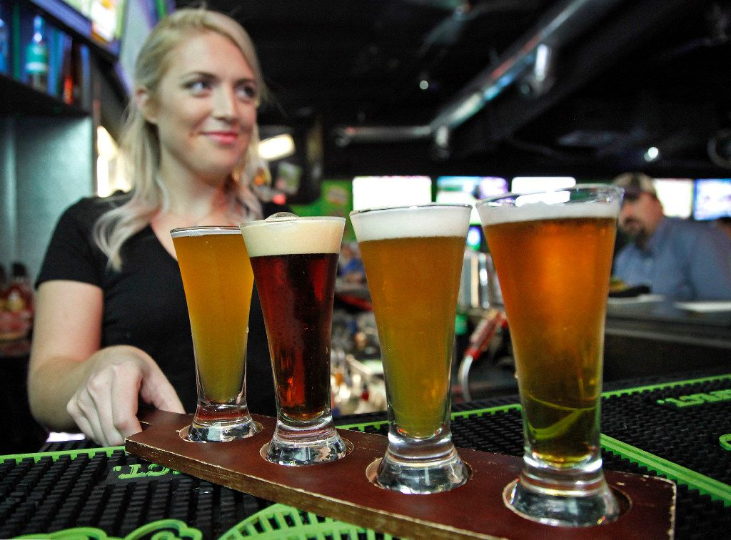 A waitress serves up a beer flight at the Drunken Donkey in Lewisville.