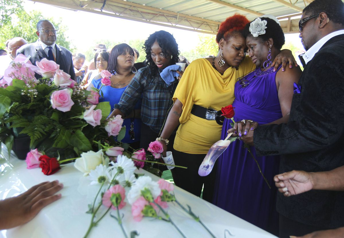 A friend comforted Vickie Cook (second from right) at the gravesite of her daughter, Deanna Cook, who authorities say was killed by her ex-husband in her home as she called 911 for help in August 2012.