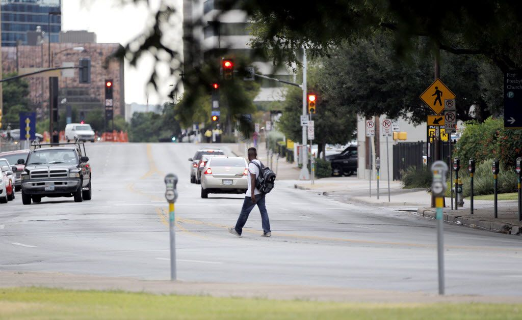 A pedestrian crosses Young Street in front of First Presbyterian Church of Dallas where one proposed DART light rail expansion route would place tracks where the current west bound lanes of Young Street are currently.