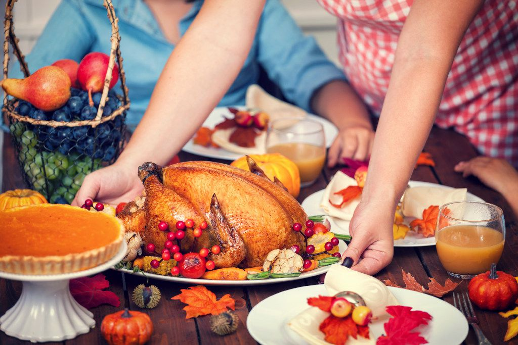 Young mother serving turkey for her family at Thanksgiving