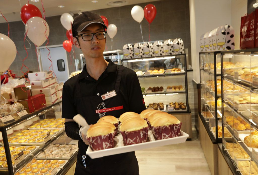 Tei Wei Chu stocks the pastry shelves during the opening of 85°C Bakery Cafe in Frisco.