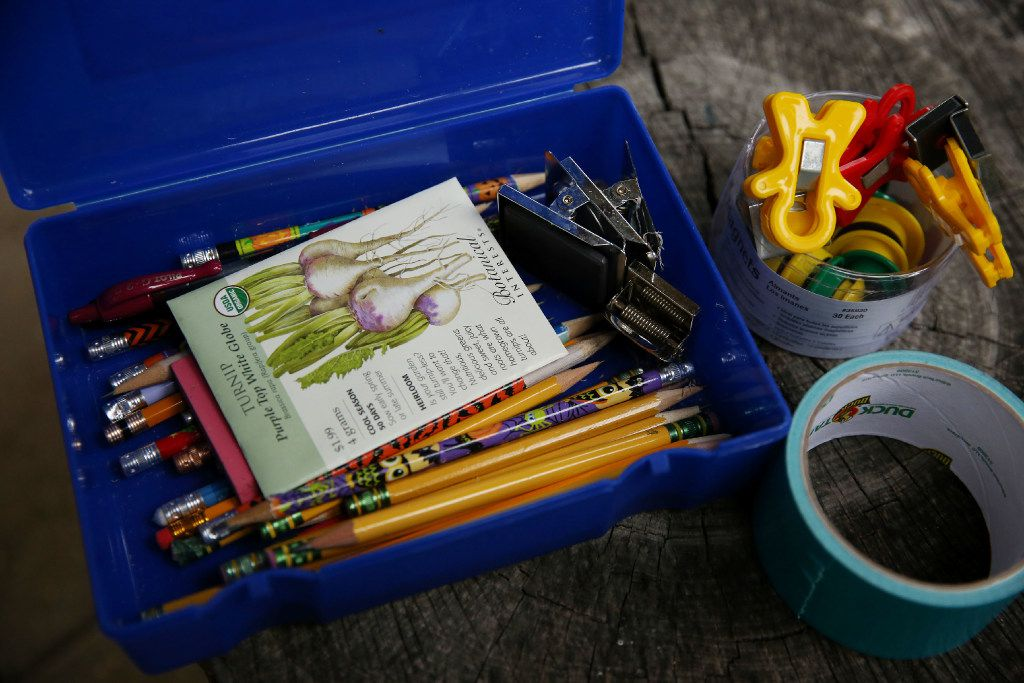 School supplies and seeds sit on a a stump under the outside classroom before Dayle Henderson, a first grade teacher, instructs students in planting seeds in the John J. Pershing Elementary School garden. (Andy Jacobsohn/The Dallas Morning News)
