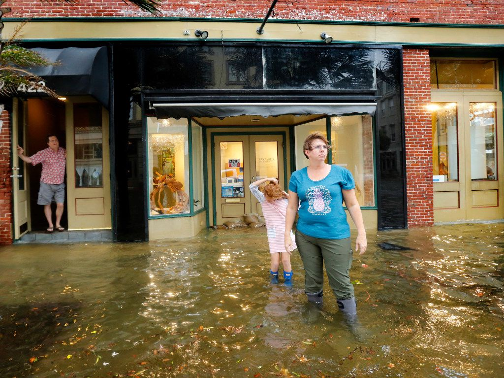 Majka Woods (right) and her daughter Anneli Kucera play in the flooded sidewalk as Tim Thompson (left) watches from the step of their residence in the historic Strand District. The city of Galveston, Texas was flooded from punishing overnight rains from Tropical Storm Harvey which passed by the island, Tuesday, August 29, 2017. Since the winds were out of the north, surge also came over the piers adding to the flooding. (Tom Fox/The Dallas Morning News)