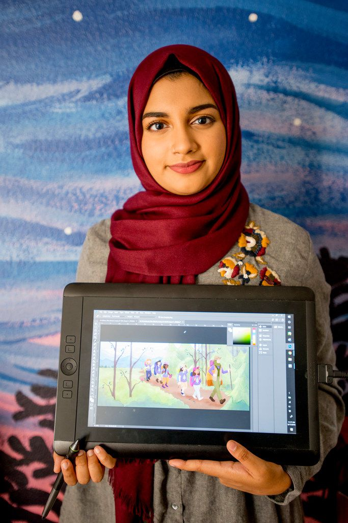 Aaliya Jaleel poses with a tablet displaying her work from Under My Hijab.