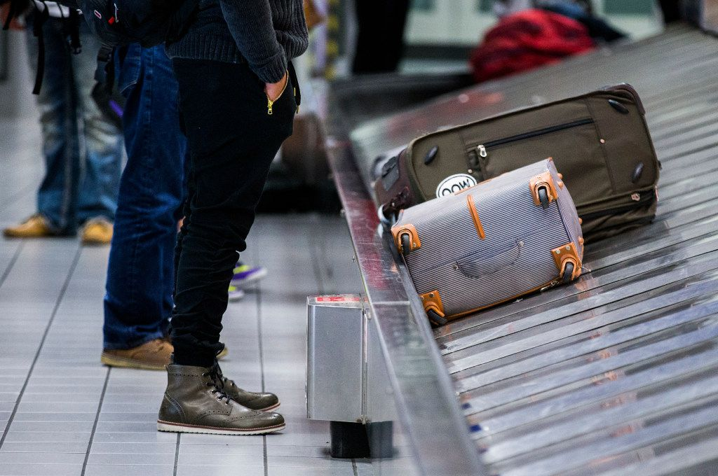 A traveler waits for his bag as luggage moves around a baggage claim at Gate C on Friday, March 10, 2017 at DFW international Airport in Dallas. (Ashley Landis/The Dallas Morning News)
