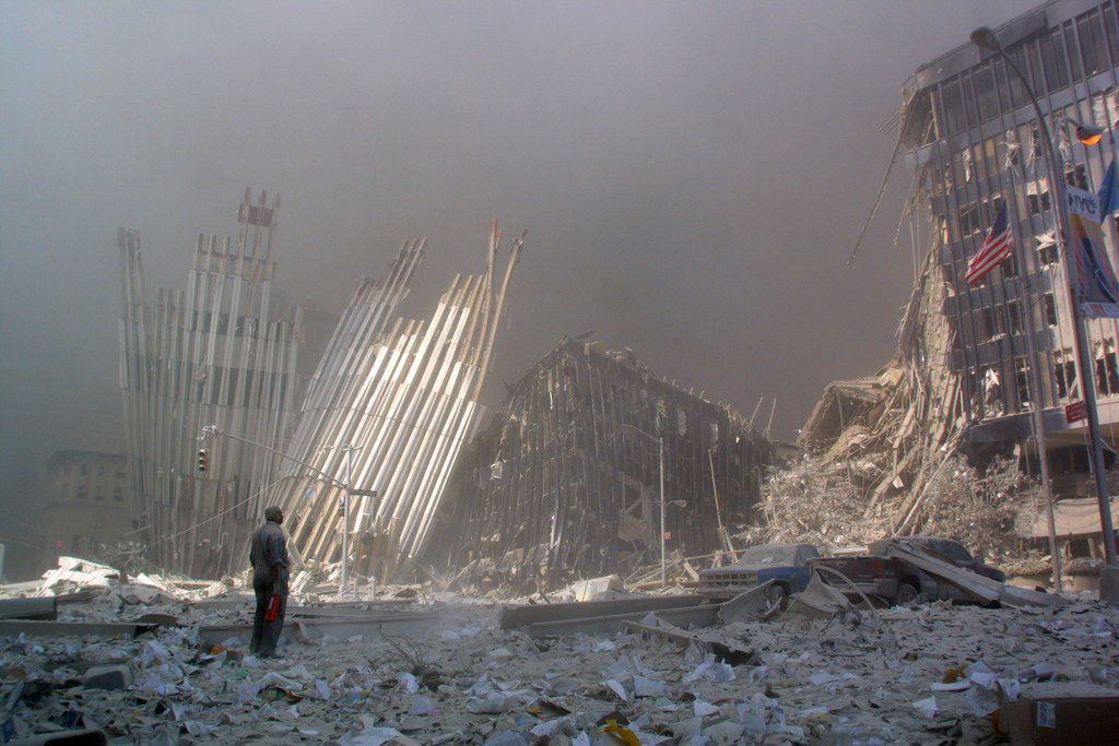 In this file photo taken on Sept. 11, 2001, a man stands in the rubble, calling out to ask if anyone needs help, after the collapse of the first World Trade Center Tower in New York City.