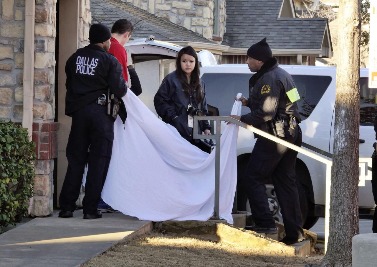 Dallas Police Department officers use a sheet to cover the doorway as the body of a two-month-old girl is removed at Rosemont at Hickory Trace apartment complex in south Dallas, January 26, 2015.