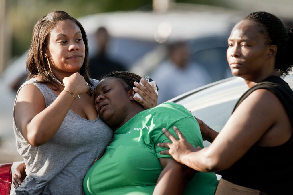 An unidentified woman is comforted near the scene of the fatal shooting of James Harper by Dallas Police in southeast Dallas on July 23, 2012. (Jeff Lautenberger/The Dallas Morning News)  -- police shooting of James Harper in the Dixon Circle community