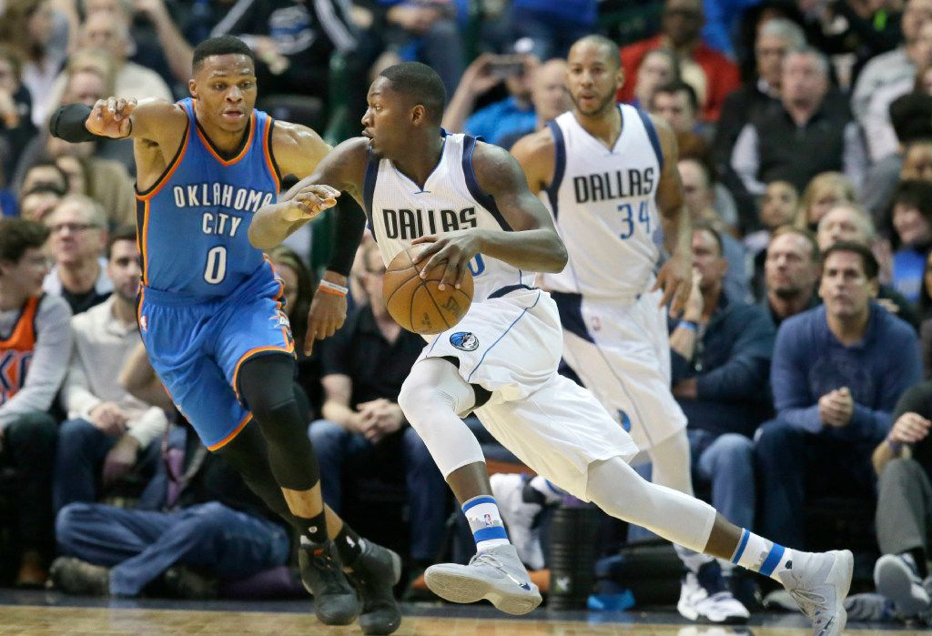 Dallas Mavericks forward Dorian Finney-Smith (10) drives against Oklahoma City Thunder guard Russell Westbrook (0) as Mavericks guard Devin Harris (34) looks on during the first half of an NBA basketball game in Dallas, Sunday, March 5, 2017. (AP Photo/LM Otero)