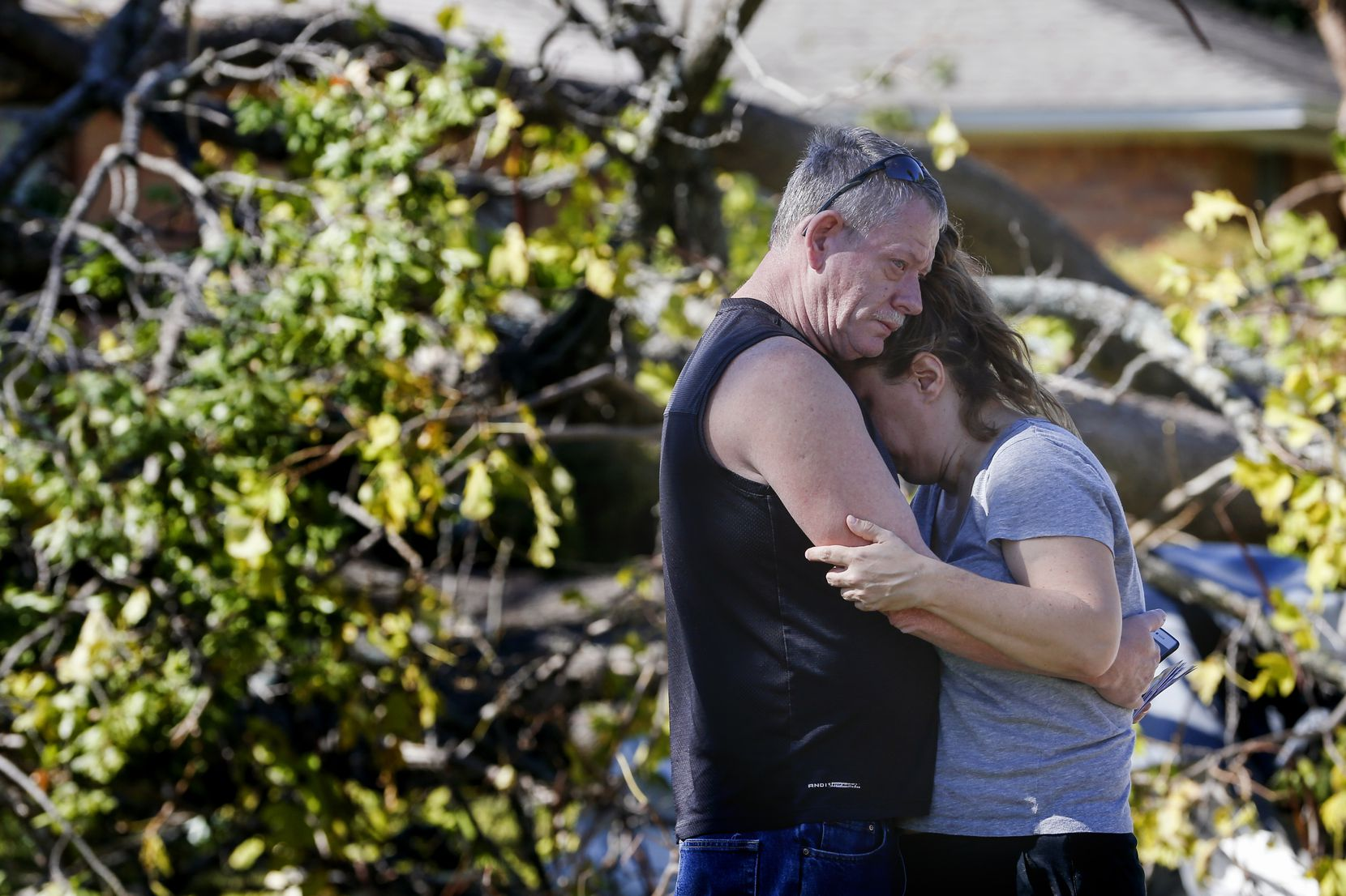 Tommy Edmonds, left, embraces his wife, Heidi Edmonds, outside of their home, which was destroyed when a tornado hit the night before, on Westway Avenue in Garland, Texas, on Sunday, Oct. 21, 2019. (Ryan Michalesko/The Dallas Morning News)