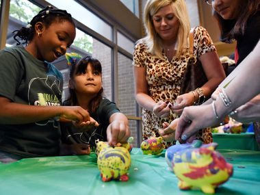 Kristin Strickland (2nd from right), principal at Arapaho Classical Magnet School in Richardson, donates pennies to piggy banks as Audelia Creek Elementary students Rodiah Babatunde (far left) and Madison Chavez, collect the money during an announcement about a new program to help students save for college.