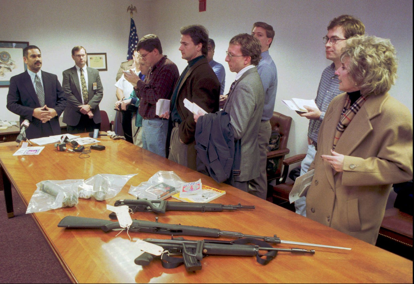 """In January 1999, FBI agent Ted Jackson (far left) showed reporters the weapons and pipe bombs confiscated after a shootout with a suspected bank robber in Columbus, Ohio. The FBI was investigating Peter Langan, known now as Donna Langan, arrested in Columbus, and Richard Lee Guthrie, arrested in Cincinnati, as the """"Midwestern Bank Bandits,"""" two bank robbers who taunted federal authorities in a string of robberies throughout the Midwest."""