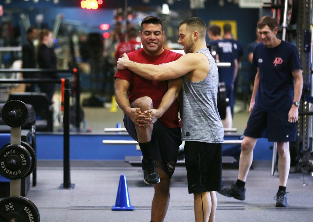 Ryan Bachik, director de REACT, ayuda a Steven Martínez, paramédico y bombero de Addison. Este gimnasia ofrece entrenamiento para prevenir lesiones. ROSE BACA/DMN