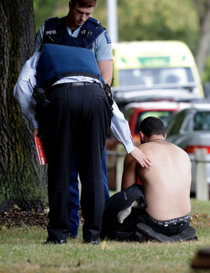 Police console a man outside a mosque in central Christchurch, New Zealand, Friday.