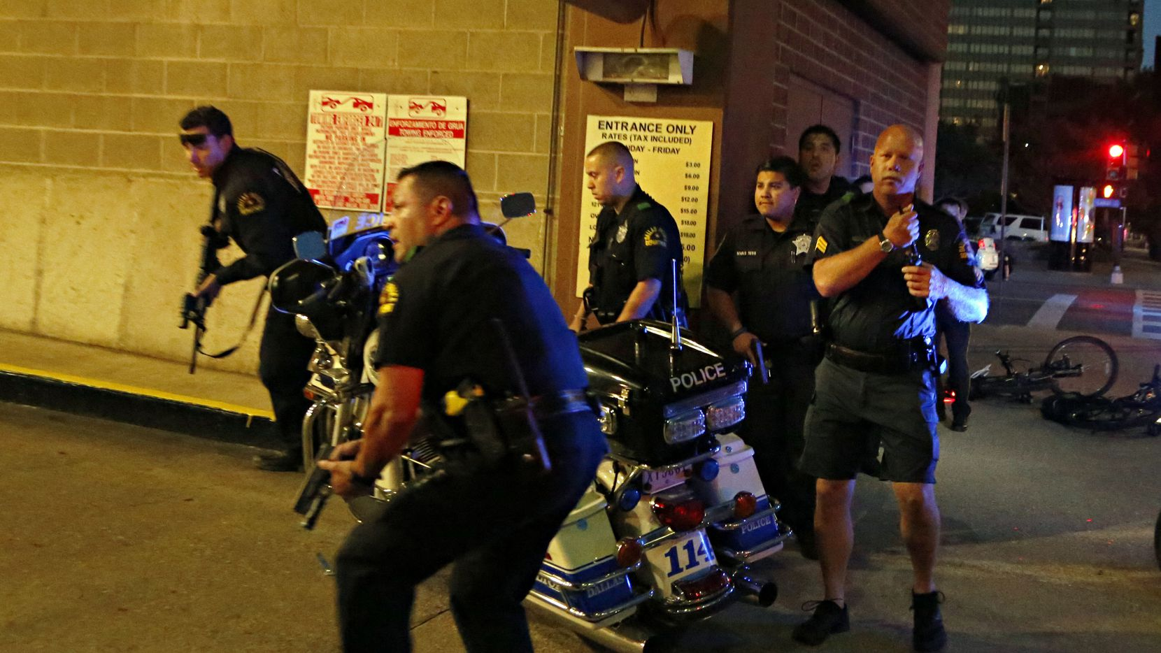 Police officers run with guns drawn into a parking garage during the deadly shooting. (G.J. McCarthy/Staff Photographer)