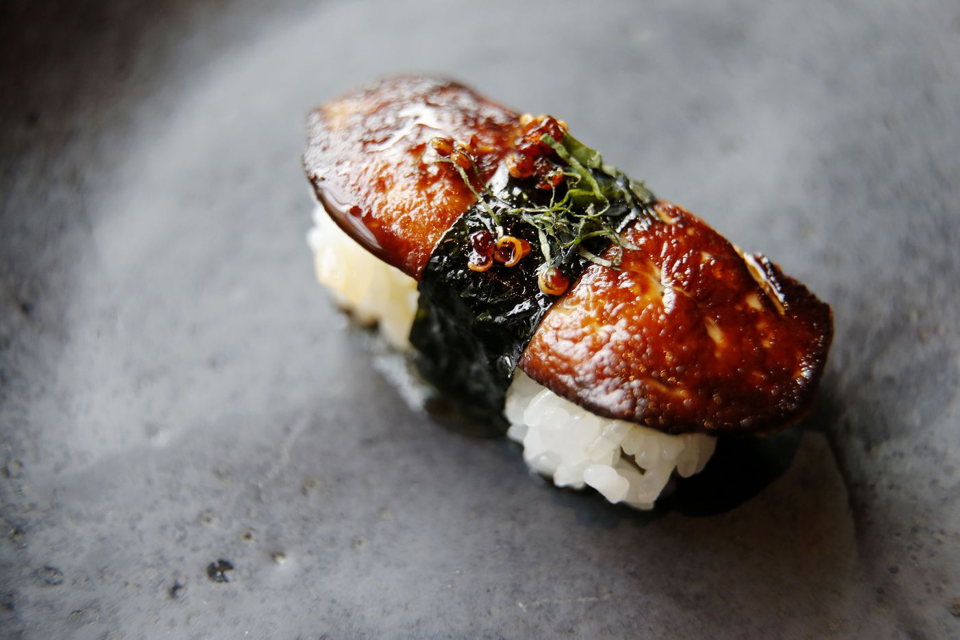 Foie gras nigiri sushi. The seared foie is brushed with fish caramel, banded with nori and garnished with candied quinoa and slivered negi.