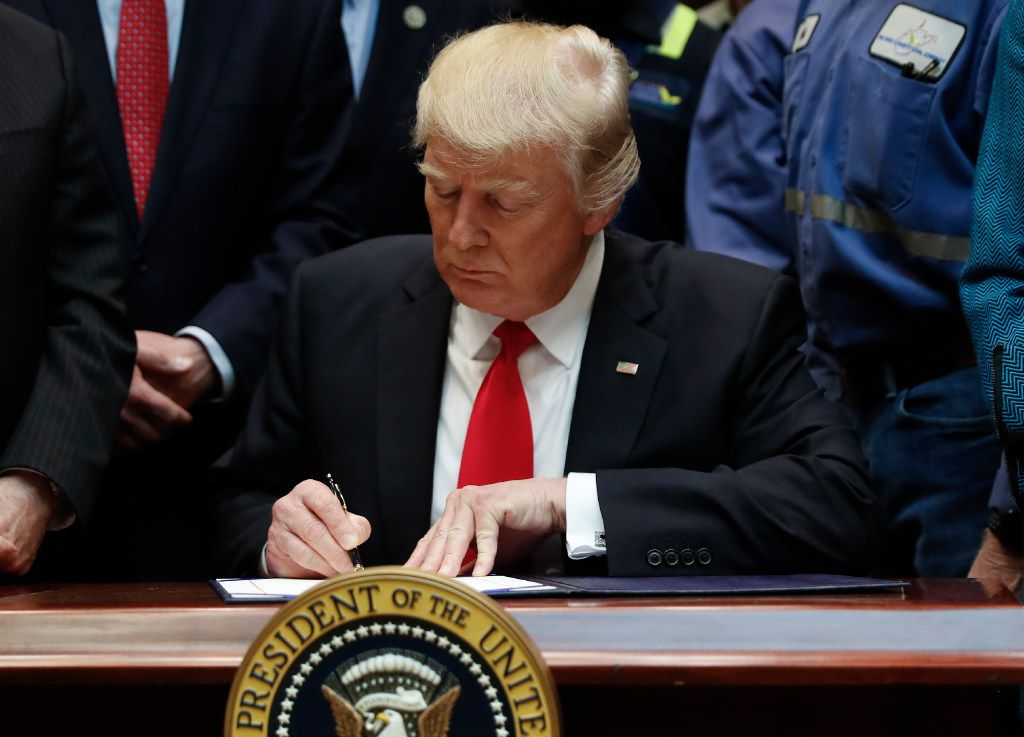 President Donald Trump signs H.J. Res. 38 in the Roosevelt Room of the White House in Washington, Thursday, Feb. 16, 2017. (AP Photo/Carolyn Kaster)