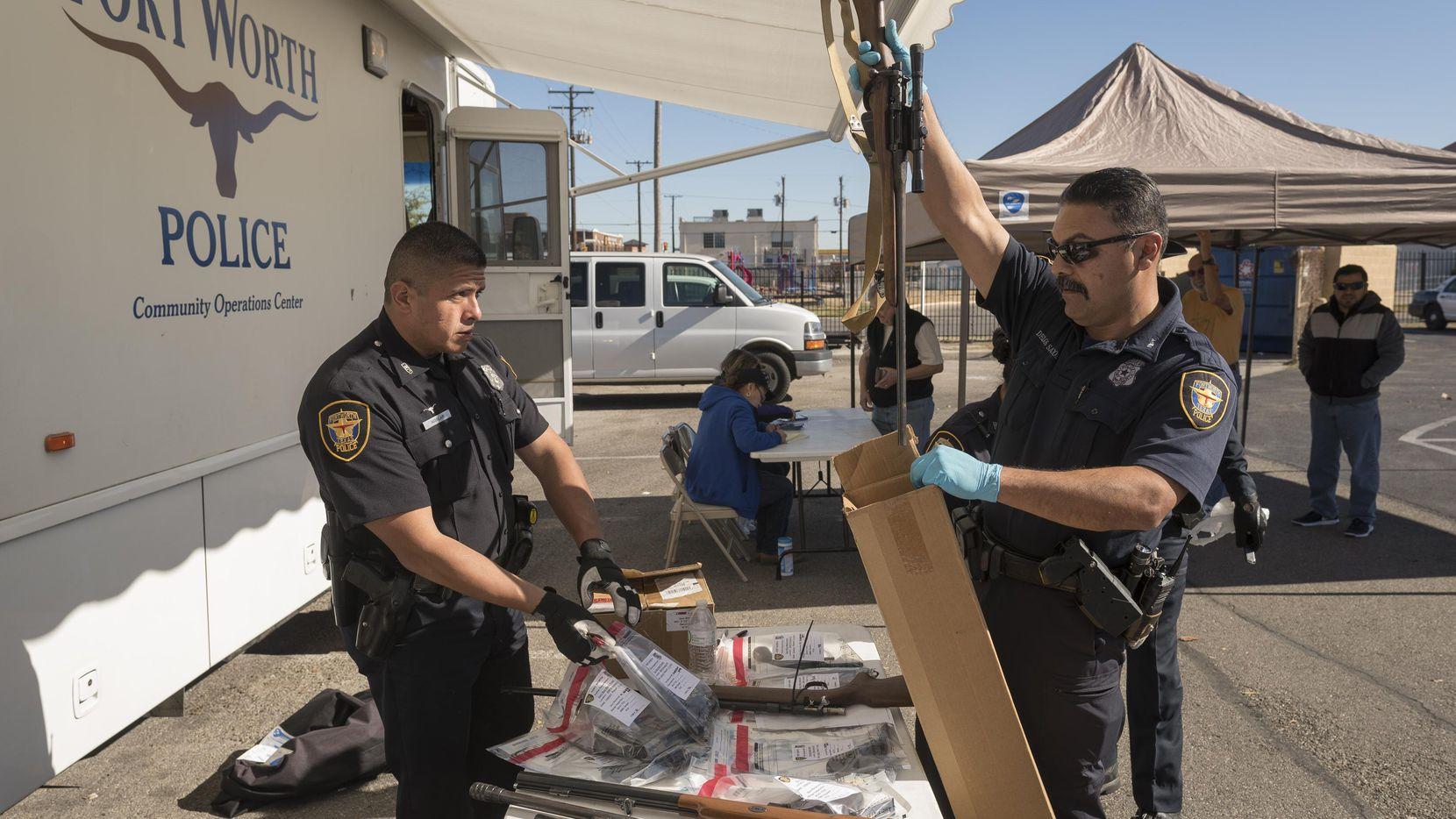 Los policías de Fort Worth JM Aguilar (izq.) y R. de los Santos reciben armas como parte de un programa para recomprarlas. (DMN/REX. C. CURRY)