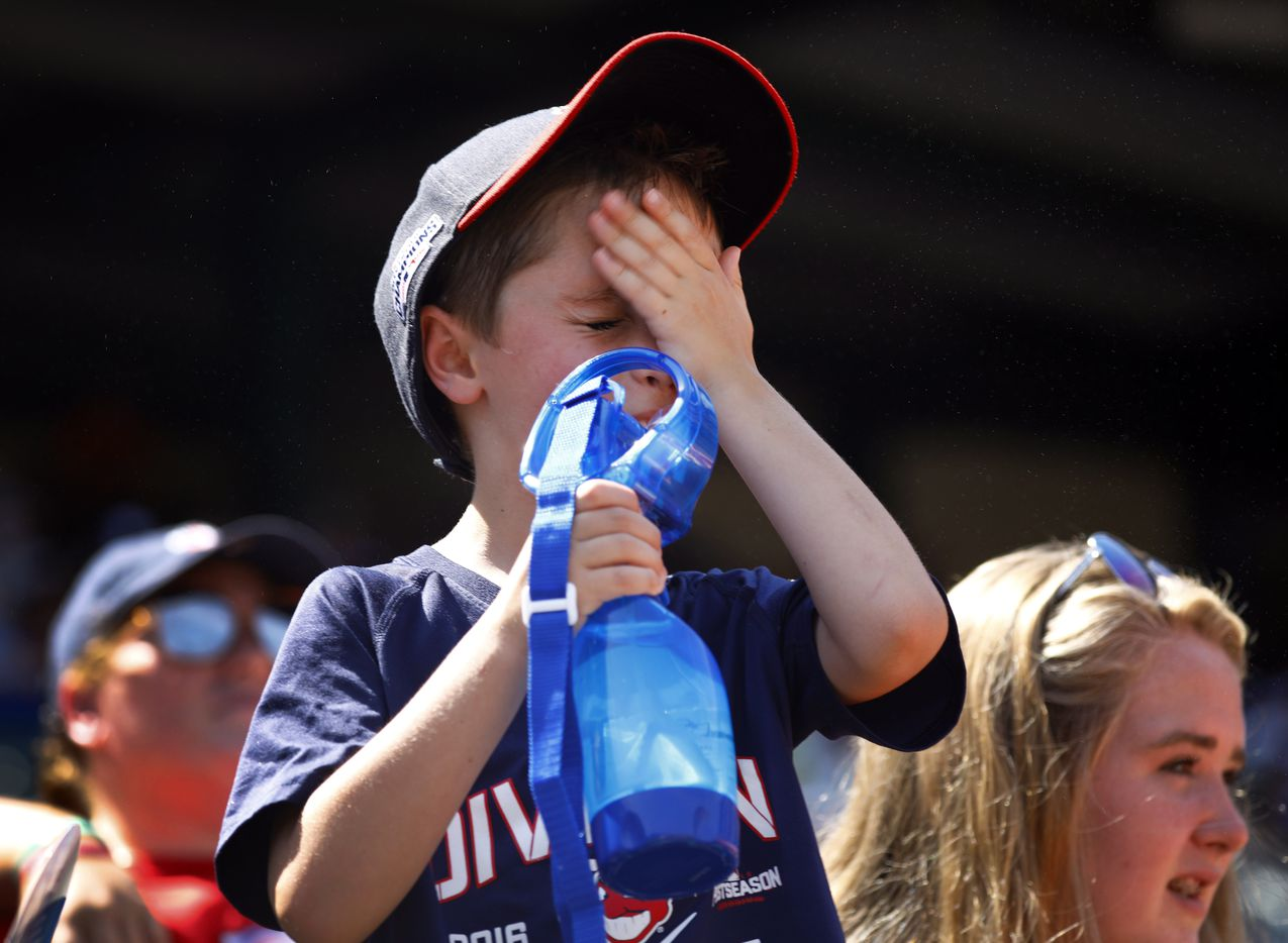 Cleveland Indians fan Brayden Adams, 6, of Southlake, Texas wipes water from his face as he cools himself with a fan at Globe Life Park in Arlington, Texas, Sunday, July 22, 2018.