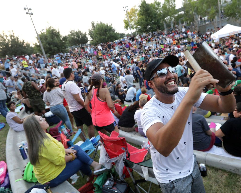 Ricardo Sanchez hits a cowbell to the beat as guests dance to the music during the Vitruvian Salsa Festival.