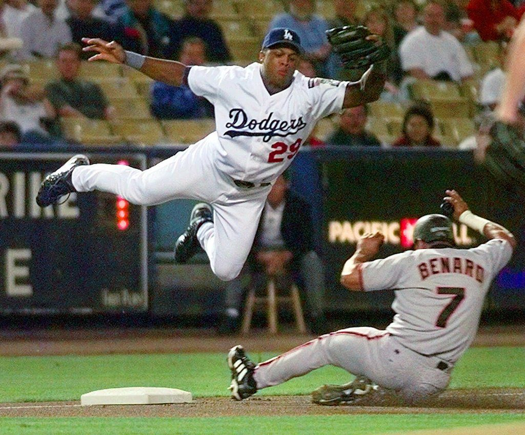 FILE - San Francisco Giants' Marvin Benard slides safely under a leaping Los Angeles Dodgers' Adrian Beltre on a wild pitch by Dodgers' Eric Gagne during the first inning, Monday, Sept. 20, 1999, in Los Angeles.