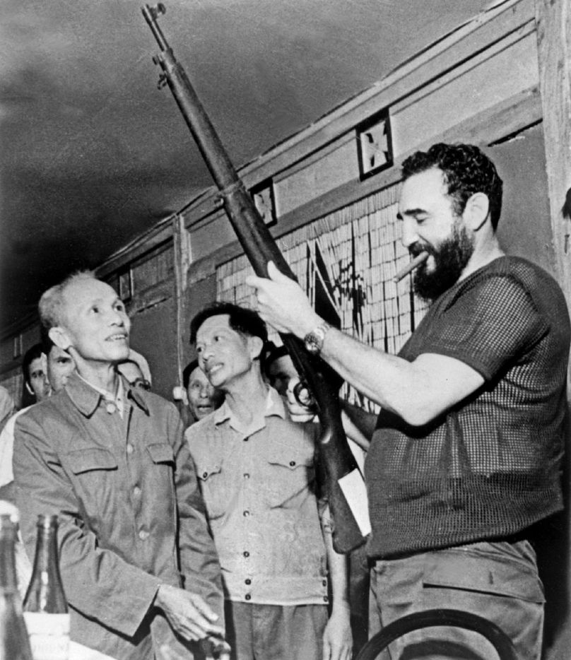 In this Sept. 1973 file photo, Cuban president Fidel Castro (R) looks at a rifle during a visit in North Vietnam during the Vietnam war.