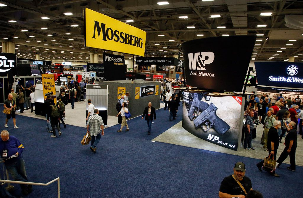 National Rifle Association convention goers walk by displays on the exhibit floor inside the Kay Bailey Hutchison Convention Center in Dallas, Friday, May 4, 2018. (AP Photo/Sue Ogrocki)