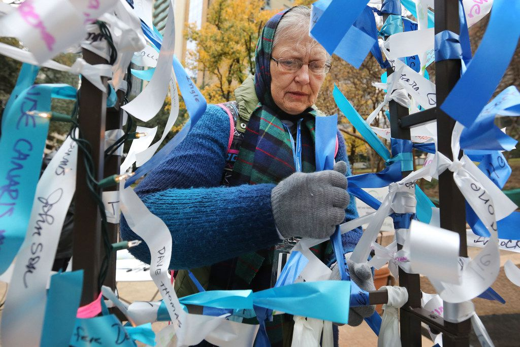 Karen Rosenkrans of Dallas ties a ribbon on a memorial in honor of her father, who served in the Army during World War II, as she attends a Pearl Harbor remembrance held at Thanks-Giving Square in downtown Dallas on Thursday, December 7, 2017. (Louis DeLuca/The Dallas Morning News)