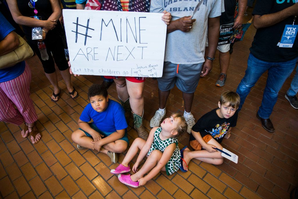 From left, Marcus Radovich, Athena Radovich and Keith Norman sit on the floor as Cassandra Radovich and Keith Norman hold a sign during a Families First Rally at the Texas Democratic Convention on Saturday, June 23, 2018 at the Fort Worth Convention Center in Fort Worth.