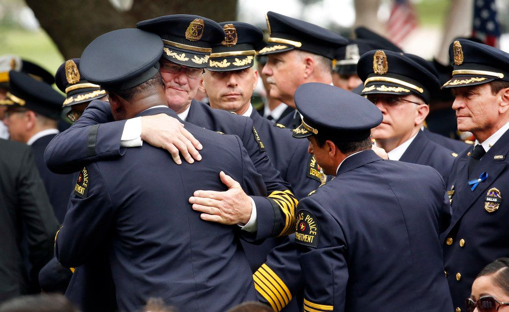 Dallas police command staff comfort one another after the burial of Officer Rogelio Santander.