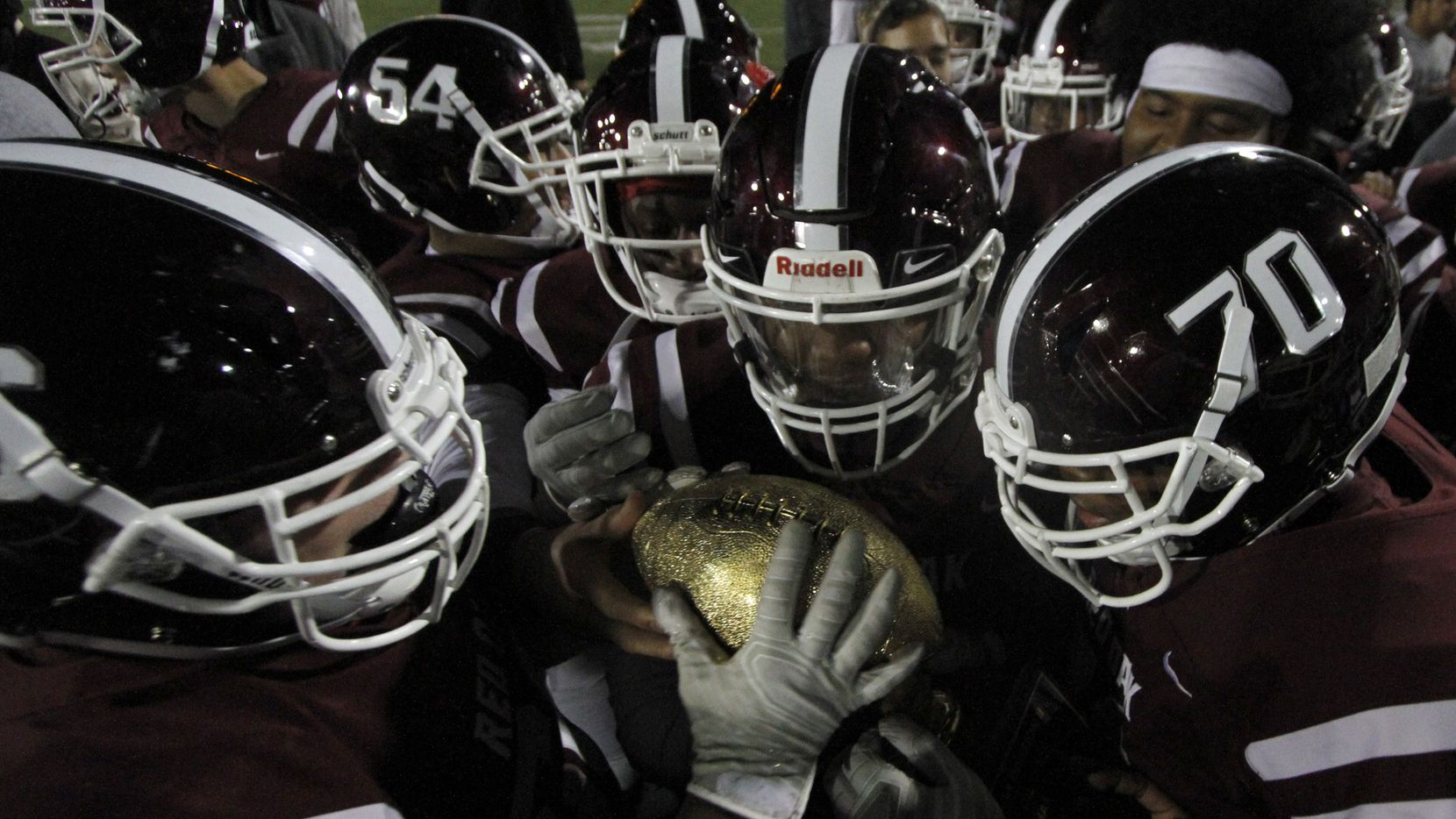 Members of the Red Oak Hawks marvel at the golden football atop a trophy presented after they finished on top of the District 6-5A Division ll competition to receive the coveted district acknowledgement. It marked the first time since 1982 that the hawks have received the honor as lone district champions. Red oak defeated Seagoville 48-13 in their regular season finale played at Billy Goodloe Stadium in Red Oak on November 7, 2019. (Steve Hamm/ Special Contributor)