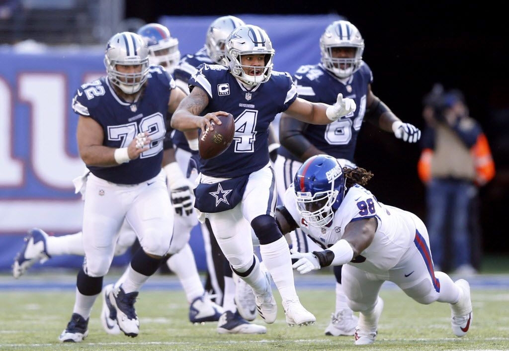Dallas Cowboys quarterback Dak Prescott (4) scrambles as he evades New York Giants defensive tackle Damon Harrison (98) on a run during the first half of play at MetLife Stadium in East Rutherford, New Jersey, on Sunday, December 10, 2017. (Vernon Bryant/The Dallas Morning News)