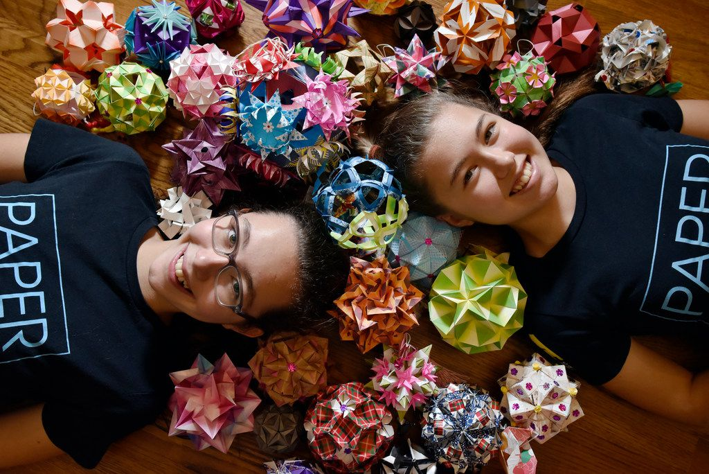 Katherine Adams, 12, (left) and her sister Isabelle Adams, 14, with origami ornaments made by volunteers for their organization Paper For Water, at their home in Dallas, July 24, 2018. Since the organization was launched, the young sisters have worked with hundreds of volunteers to raise more than $1.5 million to help fund 150 plus water projects in 14 countries.