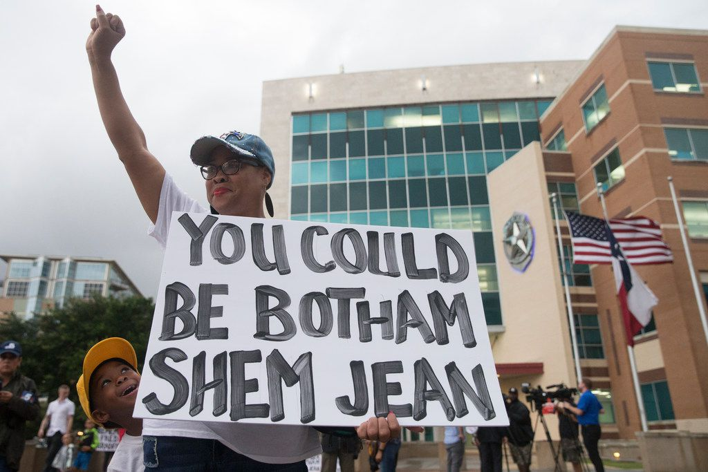 "Dr. Pamela Grayson raised her fist as ""Young King"" Solomon Grayson, 6 peaked behind her sign during a Mothers Against Police Brutality candlelight vigil for Botham Shem Jean at the Jack Evans Police Headquarters on Friday. Jean was shot by a Dallas police officer who says she mistook his apartment for hers on Thursday night."