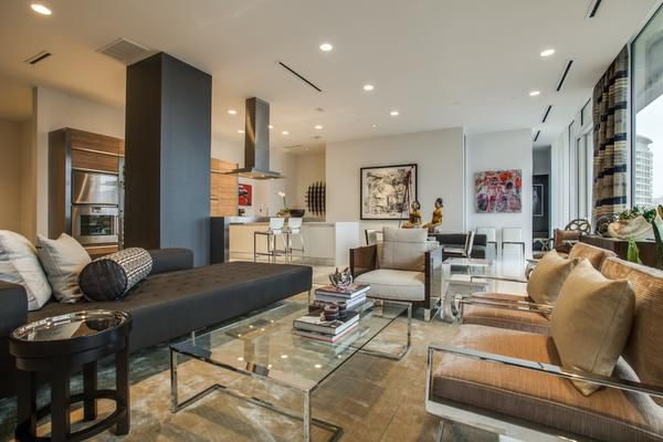 The living and dining areas of the penthouse residence are unified by contemporary upholstery in neutral tones accented with black.