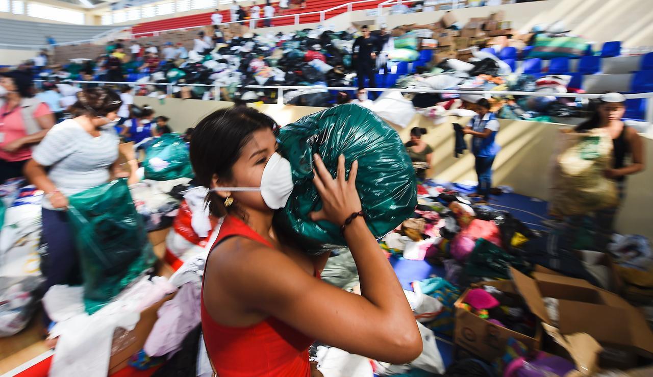 Una voluntaria ayuda a repartir vituallas para los damnificados del terremoto en Manta, Ecuador (AFP/GETTY IMAGES/LUIS ACOSTA)