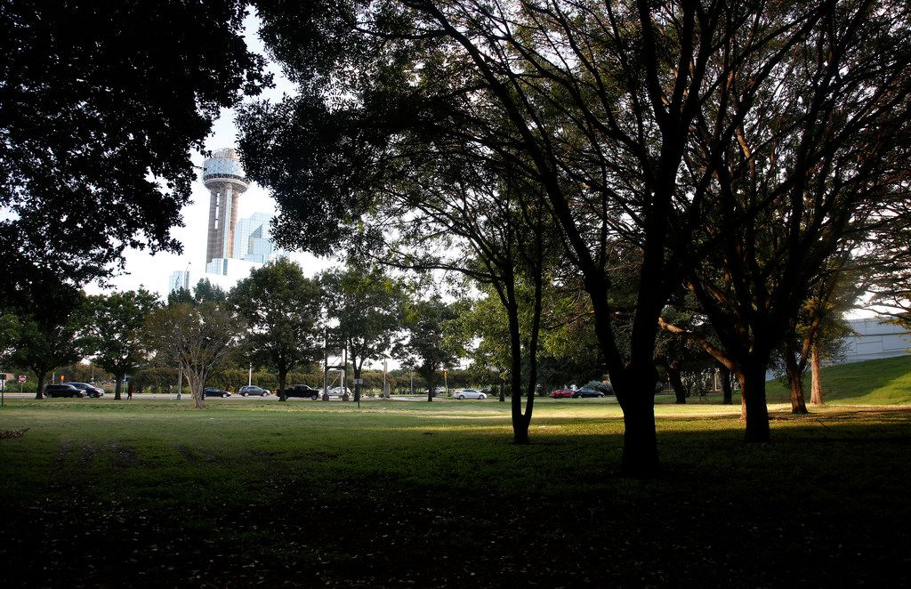 Reunion Tower is seen through the trees as downtown traffic heads west toward Stemmons Freeway past Martyrs Park in downtown Dallas.