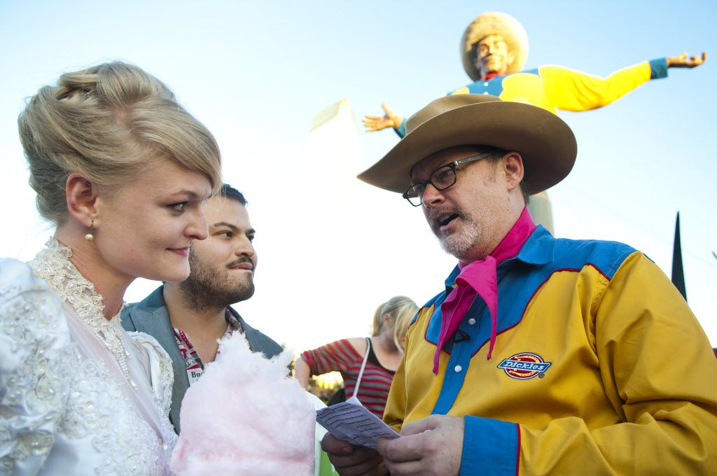 """Sara Rice of Dallas and Jose Luis Martinez Hernandez of Mexico City listened to their friend Tom """"Pinky Diablo"""" Sale of Ennis conduct their wedding ceremony in front of Big Tex at the State Fair of Texas in 2010. (File Photo/Staff)"""