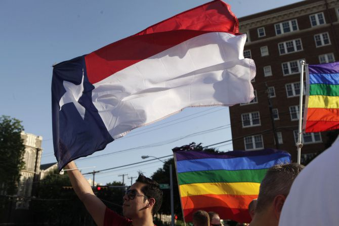 Frank Garza waved the Texas flag as members and allies of the Dallas lesbian, gay, bisexual and transgender community  gathered for the Day of Decision rally at the Legacy of Love Monument in Oak Lawn in 2014. (File 2014/Staff)