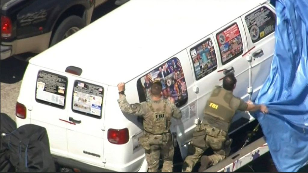 This frame grab from video provided by WPLG-TV shows FBI agents covering a van after the tarp fell off as it was transported from Plantation, Fla., on Friday. Federal agents and police officers have been examining it in connection with package bombs that were sent to high-profile critics of President Donald Trump. The van has several stickers on the windows, including American flags, decals with logos and text.