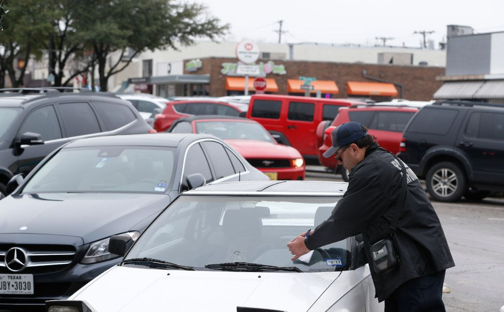 Peter Gonzales with University Park police parking enforcement puts a ticket on a car for parking in an undesignated spot at Snider Plaza in Dallas on January 18, 2017.