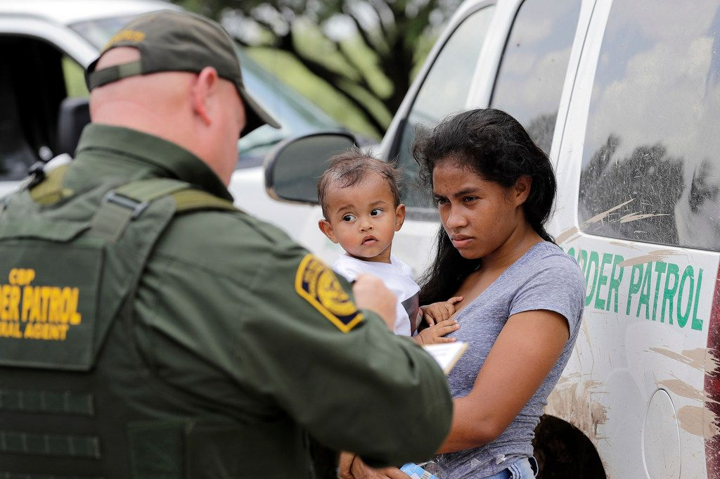 A mother migrating from Honduras holds her 1-year-old child as she surrenders to U.S. Border Patrol agents after illegally crossing the border Monday, June 25, near McAllen.
